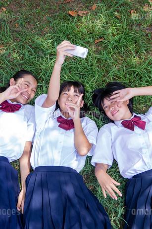草の上に寝転がって写真を撮る中学生の写真素材 [FYI02545479]