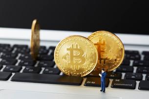 キーボードの上に立てられたビットコインとミニチュアの写真素材 [FYI02545534]