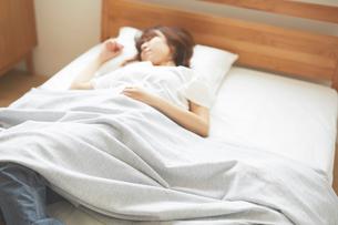 ナチュラルなベッドで眠る女性の写真素材 [FYI02546355]