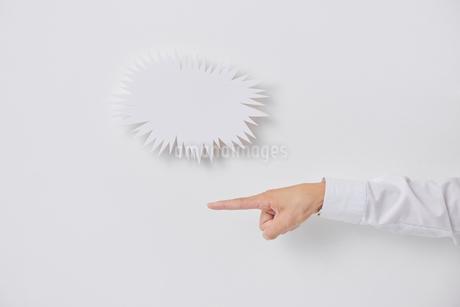 ギザギザの吹き出しと指を差す人の手の写真素材 [FYI02546372]