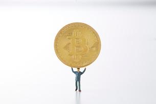 ビットコインを持ち上げるミニチュアのサラリーマンの写真素材 [FYI02547410]