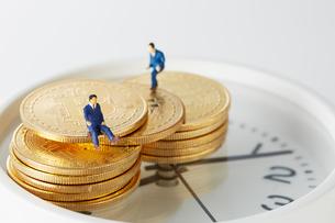時計の上に置かれたビットコインの上のミニチュアサラリーマンの写真素材 [FYI02547501]