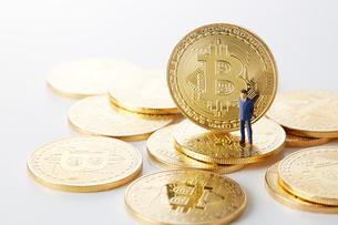 ビットコインの上のミニチュアのサラリーマンの写真素材 [FYI02547502]