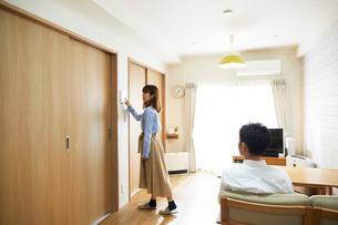 リビングルームにあるインターフォンをみる女性の写真素材 [FYI02547528]