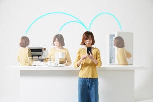 スマートフォンで家電を操作する女性の写真素材 [FYI02547529]