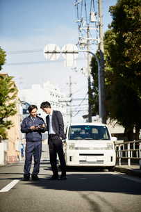 車の前で立ち話をしている二人の男性の写真素材 [FYI02547531]