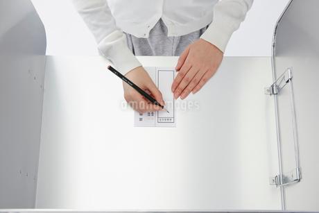 投票記載台を使用している女性の手元の写真素材 [FYI02547534]