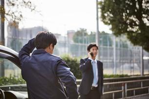 車の横に立つ男性と電話をかける男性の写真素材 [FYI02547535]