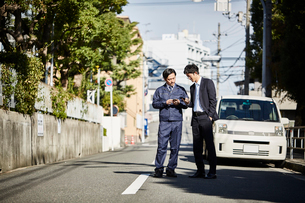 車の前で立ち話をしている二人の男性の写真素材 [FYI02547536]