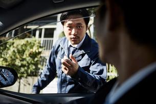 車の外から車の中に居る人に話しかける男性の写真素材 [FYI02547545]