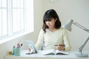 タブレットPCを使って勉強する女子高生の写真素材 [FYI02547549]