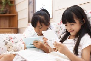 ソファでゲームをして遊ぶ女の子の写真素材 [FYI02548534]