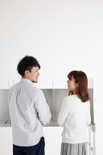 投票記載台の前に立って微笑み合う男性と女性の写真素材 [FYI02548783]