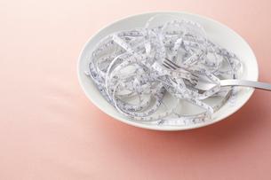 白い皿の上に乗せられたメジャーとシルバーのフォークの写真素材 [FYI02548785]