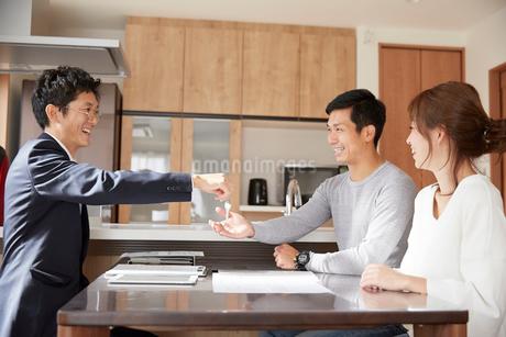 不動産屋から鍵をもらう夫婦の写真素材 [FYI02548792]