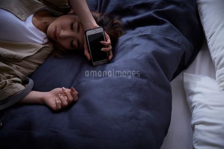 ネイビーのカバーのベットに倒れこむ暗い表情の女性の写真素材 [FYI02550143]