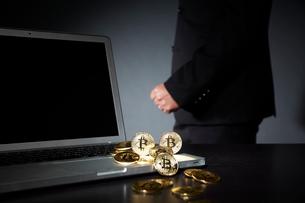 ビットコインとパソコンとスーツを着た男性の写真素材 [FYI02550257]