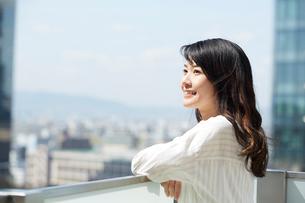 高層ビルの屋上に立つ笑顔の女性の写真素材 [FYI02550404]