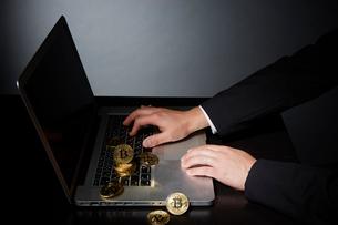 パソコンでビットコインのビジネスをするスーツを着た男性の写真素材 [FYI02551543]