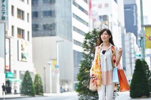 街で紙袋を持って歩く女性の写真素材 [FYI02554862]