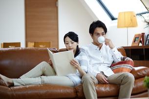 ソファで寛ぐ若い夫婦の写真素材 [FYI02555654]