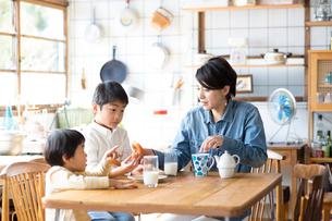 キッチンのテーブルでドーナツを食べる兄弟と母親の写真素材 [FYI02561159]