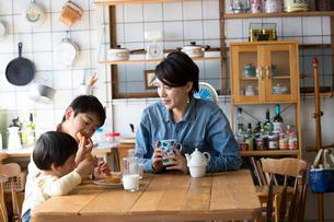 キッチンのテーブルでドーナツを食べる兄弟と母親の写真素材 [FYI02561185]