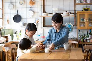 キッチンのテーブルでドーナツを食べる兄弟と母親の写真素材 [FYI02561198]