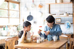 キッチンのテーブルでドーナツを食べる兄弟と母親の写真素材 [FYI02561210]