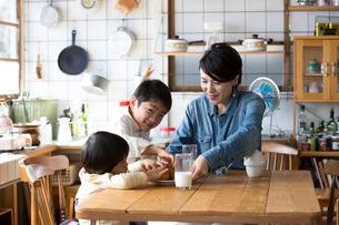 キッチンのテーブルでドーナツを食べる兄弟と母親の写真素材 [FYI02561258]