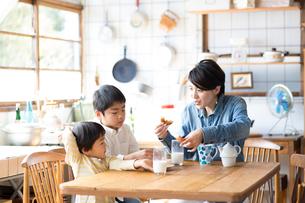 キッチンのテーブルでドーナツを食べる兄弟と母親の写真素材 [FYI02561310]
