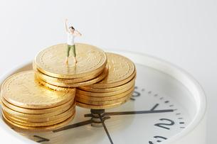 時計の上に置かれたビットコインの上のミニチュアの写真素材 [FYI02561355]