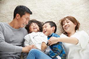 リビングで寝転がる家族の写真素材 [FYI02561370]