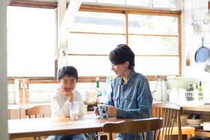 ダイニングテーブルにつく母親と男の子の写真素材 [FYI02561415]