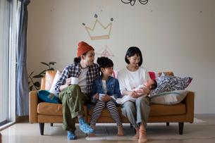 リビングのソファーに座ってくつろぐ家族の写真素材 [FYI02562424]