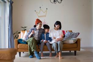 リビングのソファーに座ってくつろぐ家族の写真素材 [FYI02562456]