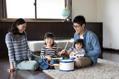 手作りの楽器のおもちゃで遊ぶ姉妹とそれを見守る両親の写真素材 [FYI02562537]
