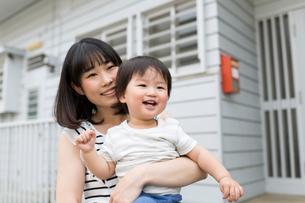 家の前で手を振る母親と子供の写真素材 [FYI02562697]