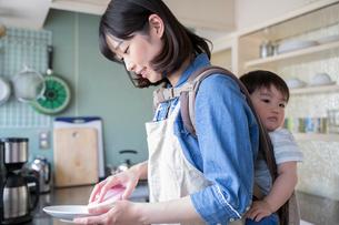 こどもをおぶってキッチンで食器を洗う母親の写真素材 [FYI02562998]
