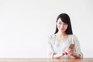 スマートフォンを持つ女性の写真素材 [FYI02564452]