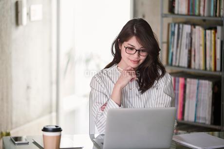 オフィスでノートパソコンを開き仕事をする女性の写真素材 [FYI02564688]
