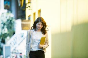 ビルの前を歩く女性の写真素材 [FYI02564743]