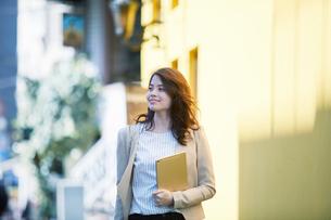 ビルの前を歩く女性の写真素材 [FYI02564771]
