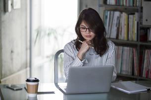 オフィスでノートパソコンを開き仕事をする女性の写真素材 [FYI02564891]