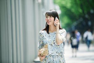 スマートフォンを持ち街を歩く女性の写真素材 [FYI02564963]