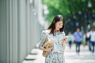スマートフォンを持ち街を歩く女性の写真素材 [FYI02565262]