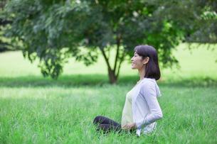 緑の中でヨガをする女性の写真素材 [FYI02565408]