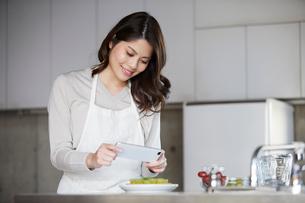 キッチンに立ち写真を撮る女性の写真素材 [FYI02565708]