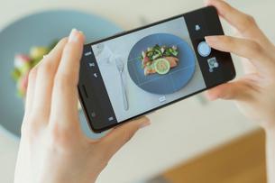 食事をスマートフォンで撮影する女性の写真素材 [FYI02568125]