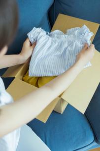 服を手に取る女性の写真素材 [FYI02568251]